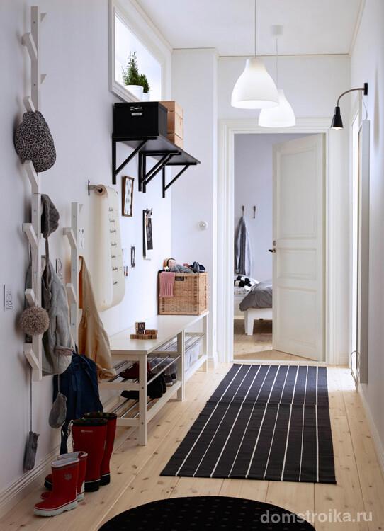 Светлый коридор с ярким освещением в виде парных ламп на потолке и отдельного освещения у зоны зеркала