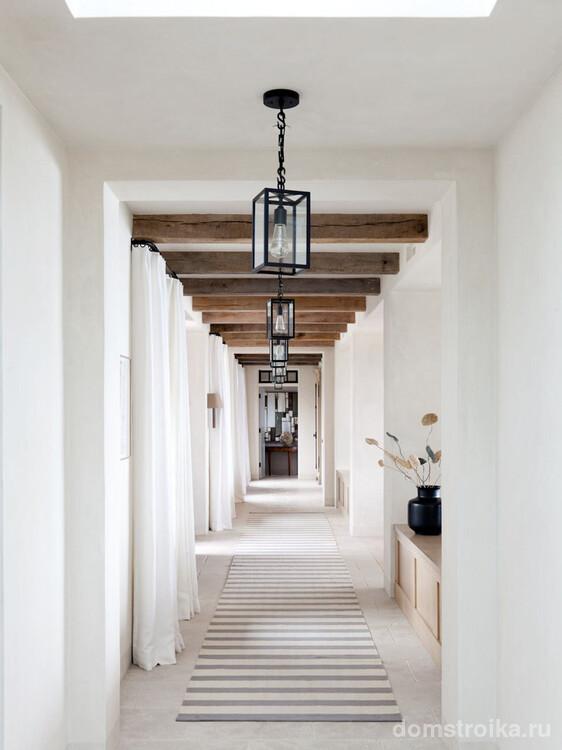Узкий коридор в светлых тонах с рядом ламп, что равномерно освещают все помещение