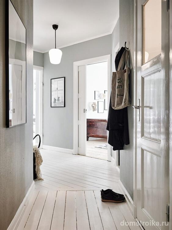 Г-образный коридор в просторной квартире в светлых тонах