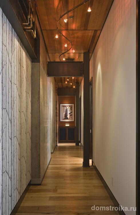 Просторный коридор в светлых тонах, освещенный яркими светильниками, что визуально еще увеличивает пространство
