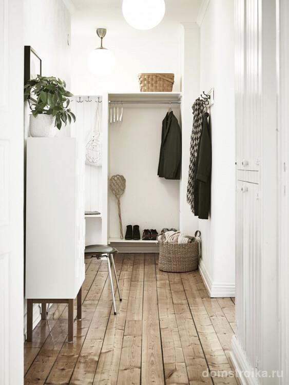 Достаточно уютное помещение коридора квартиры с парой ламп в больших белых матовых плафонах, что отлично рассеивают свет по всему пространству
