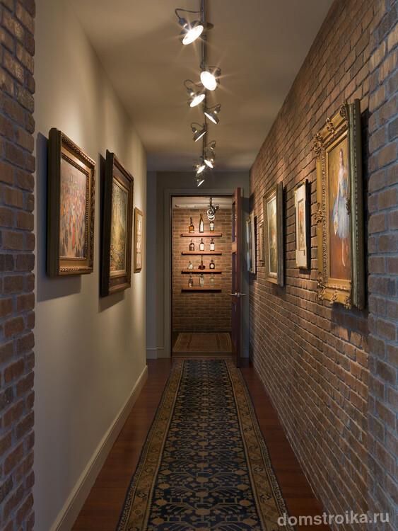 Необычное решение для узкого коридора квартиры – стены, оформленные кирпичной кладкой, которую подчеркивает оригинальная конструкция освещения