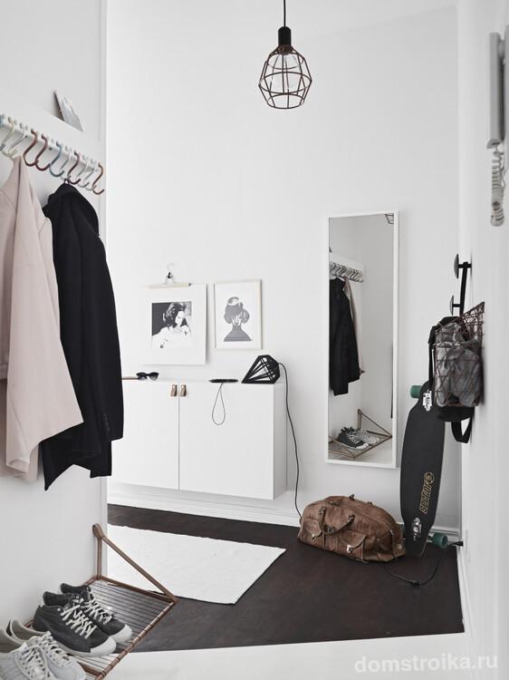 Контрастное сочетание светлых стен и темного пола создает атмосферу легкости, не перегружая пространство в г-образном коридоре