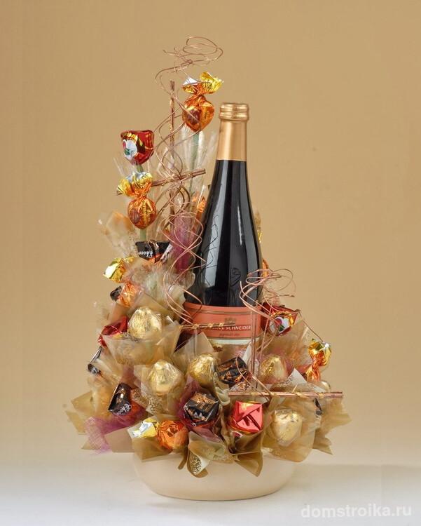 Оригинальная конструкция из конфет вокруг шампанского